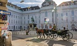 Städtereise Wien: Am harmonischen Josefsplatz, der an drei Seiten von der Wiener Hofburg begrenzt wird, fährt ein traditioneller Fiaker vorbei. Im Zentrum des Platzes steht ein Reiterstandbild von Kaiser Joseph II. (1741 - 1790), er folgte seiner Mutter Maria Theresia auf den Thron.