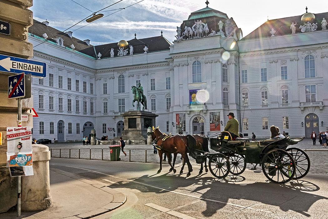 Wien: 18 Sehenswürdigkeiten in der Weltstadt an der Donau Städtereise Wien: Am harmonischen Josefsplatz, der an drei Seiten von der Wiener Hofburg begrenzt wird, fährt ein traditioneller Fiaker vorbei. Im Zentrum des Platzes steht ein Reiterstandbild von Kaiser Joseph II. (1741 - 1790), er folgte seiner Mutter Maria Theresia auf den Thron.