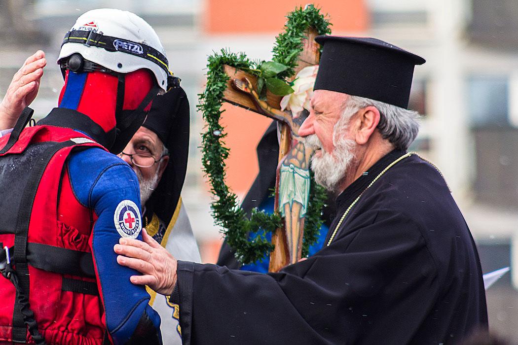 Das Ziel ist erreicht, Weihbischof Evmenios von Lefka und Erzpriester Apostolos Malamoussis, loben und segnen den Überbringer des Kreuzes.
