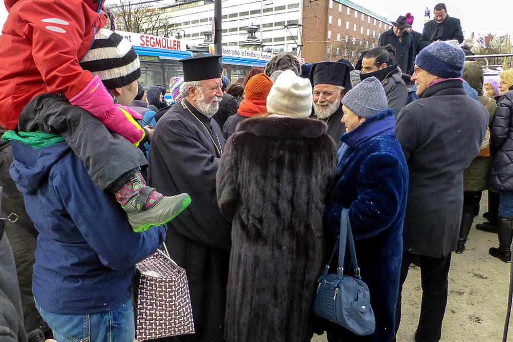 Erzpriester Apostolos Malamoussis (links) und Weihbischof Evmenios von Lefka beim Plaudern mit Mitgliedern der Kirchengemeinde.