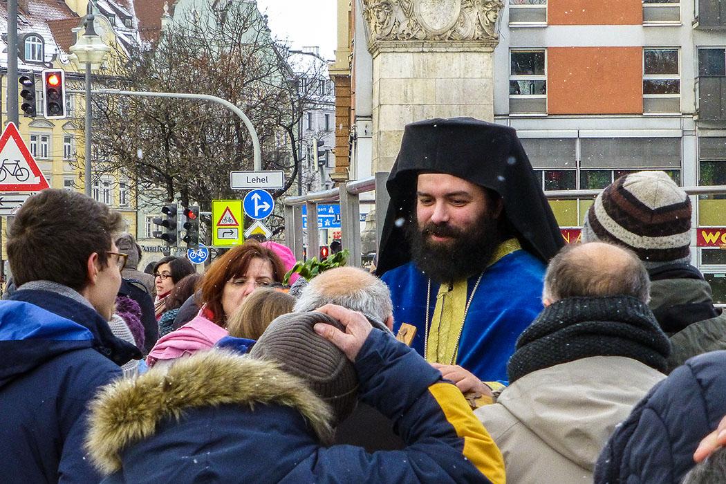 Archimandrit Georgios Siomos reicht den Gläubigen das Holzkreuz.