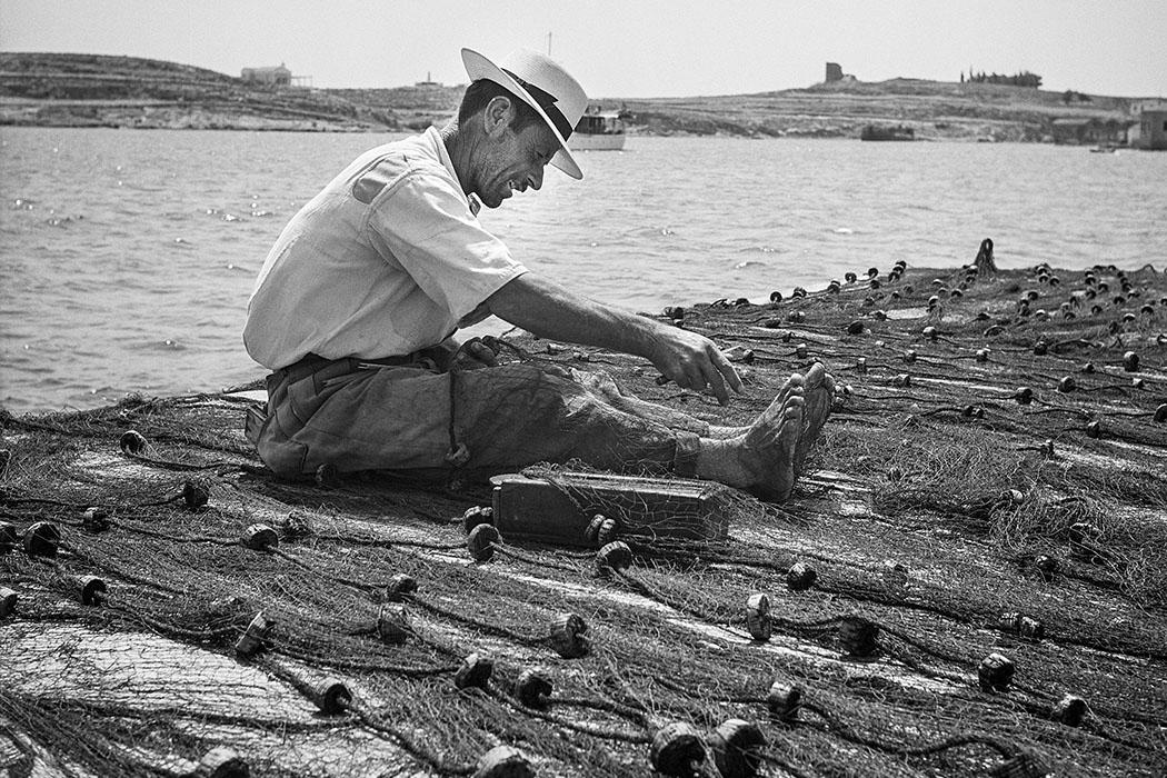 Ein griechischer Fischer bei der Reparatur der Netze. Foto © Robert McCabe