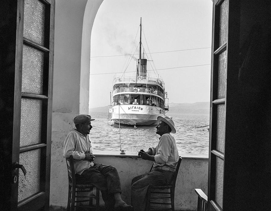 """Insel Santorin: Männergespräche in der Hafenbar mit Blick auf das Dampfschiff """"Aigaion"""". Foto © Robert McCabe"""