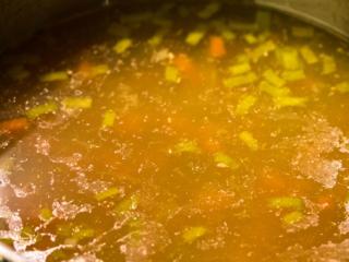 Das Huhn aus der Brühe heben und abkühlen lassen und die Brühe mit dem Gemüse erneut aufkochen lassen.