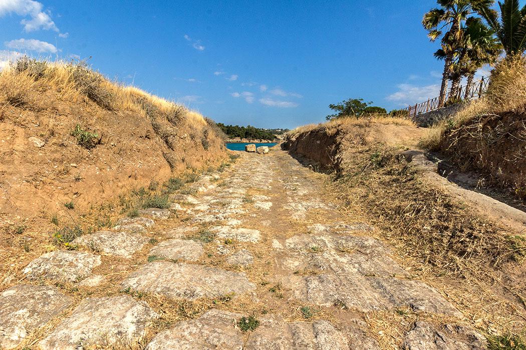 Online-Reiseführer: Peloponnes - Das antike Korinth korinth diolkos posidionia peloponnes griechenland Der Diolkos ist eine breite gepflasterte Schleifstraße, die Korinth im 7. Jhd. v. Chr. quer über die schmale Meerenge anlegte. Ganze Handelsschiffe, mit Zugtieren oder auch Menschen wurden auf dem Diolkos gezogen.