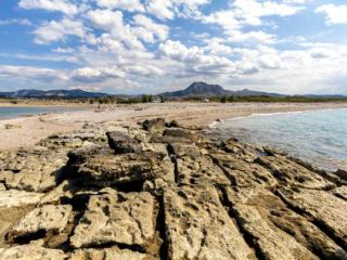 Blick von der westlichen Hafenmole des antiken Korinth zum dominanten Berg Akrokorinth.