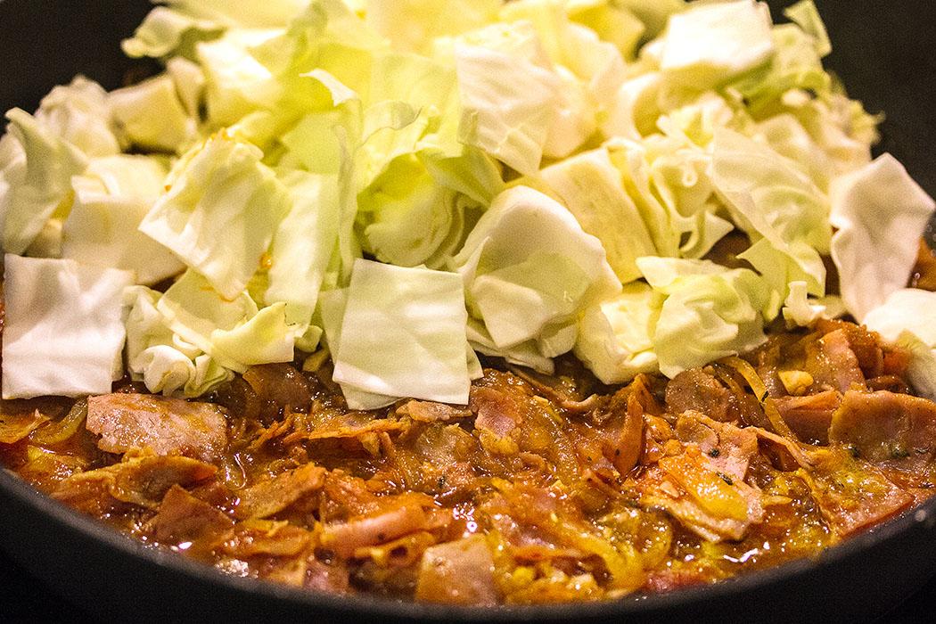 Jetzt den Weißkohl mit Apfelessig und Brühe in die Pfanne geben, salzen und abgedeckt etwa 15 Minuten bei reduzierter Hitze schmoren.