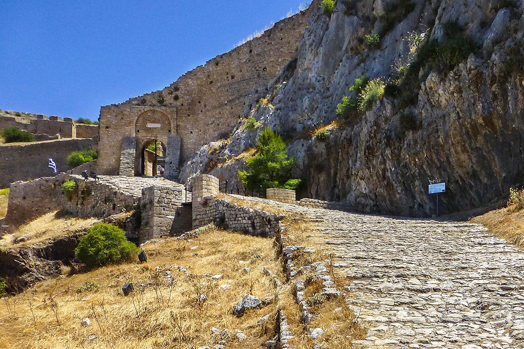 Der Aufgang zum ersten Burgtor führt direkt unter einer steilen Felswand entlang.