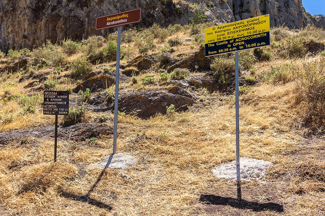 Vor dem Aufgang zur Burg weisen Schilder auf die Öffnungszeiten hin.