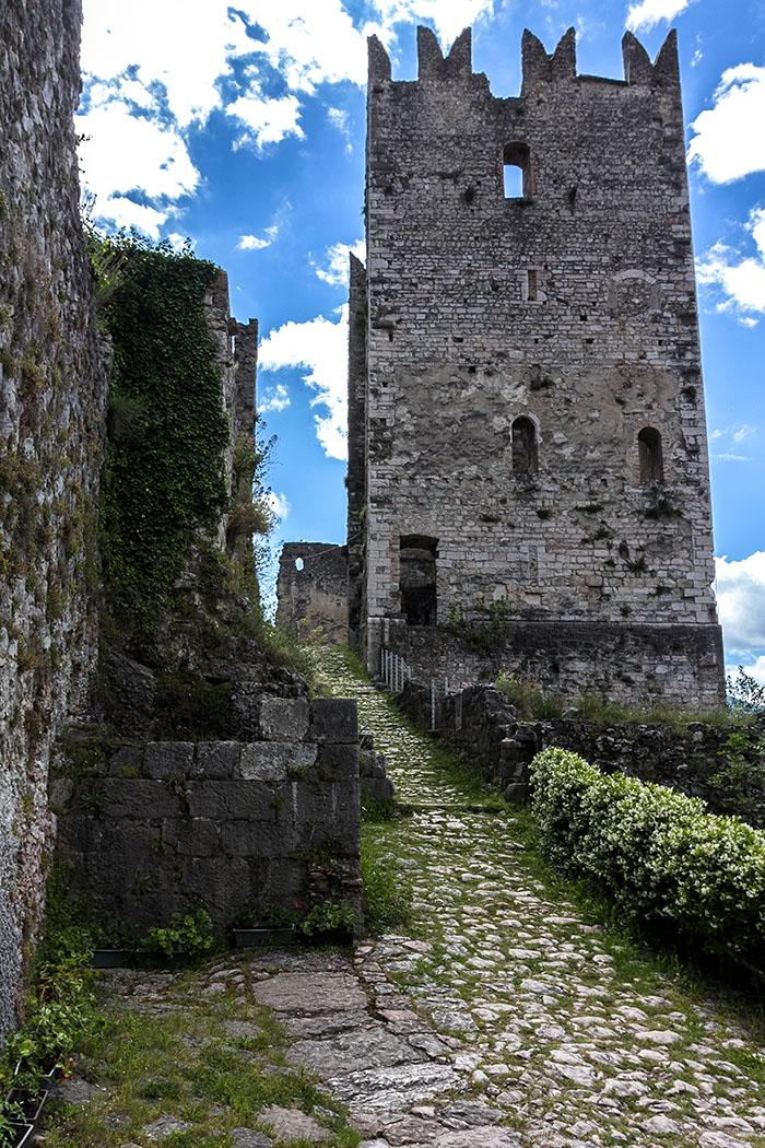 Ein gepflasterter Zugang führt romanischen Wohnturm der Burg von Arco.