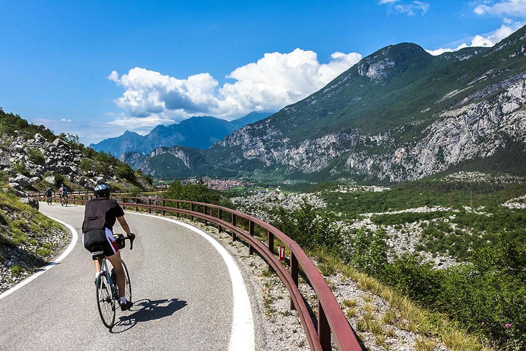 garda trentino arco marocche radfahren sport riva del garda gardasee italien Das Gebiet bei Arco ist ein Eldorado für Radfahrer. Die Roadbiker auf dem Foto sind im Gebiet der Marocche di Dro, im Sarcatal unterwegs. Am Talende ist bereits der Burgfelsen von Arco sichtbar.