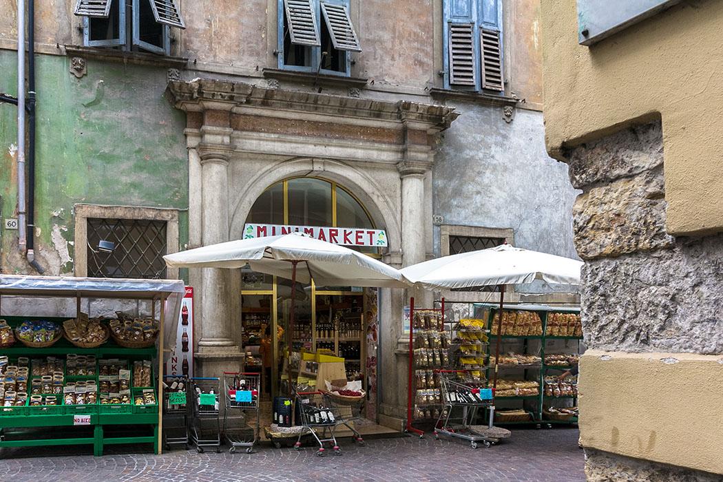 Der Minimarkt in Altstadtgassen von Arco, mit seinem eindruckvollen säulenflankierten Eingang, wirkt wie aus der Zeit gefallen.
