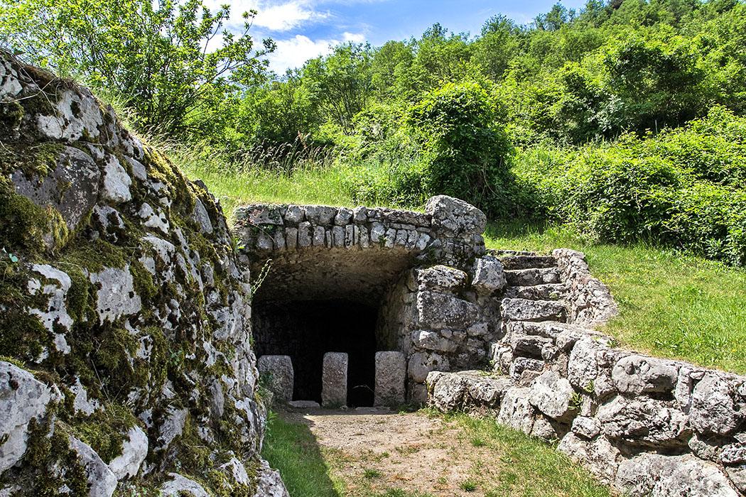 Der römische Brunnen: Sein breiter Zugang zum Wasserbecken ist auf beiden Seiten mit Steinmauern eingefasst, die sich verjüngen. Am Brunnenhaus führt eine Steintreppe nach oben.