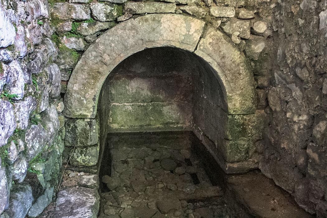 Hier wird das Wasser, das aus einer Grundwasserschicht stammt, unter einem Steinbogen in einem rechteckigen Becken gesammelt.