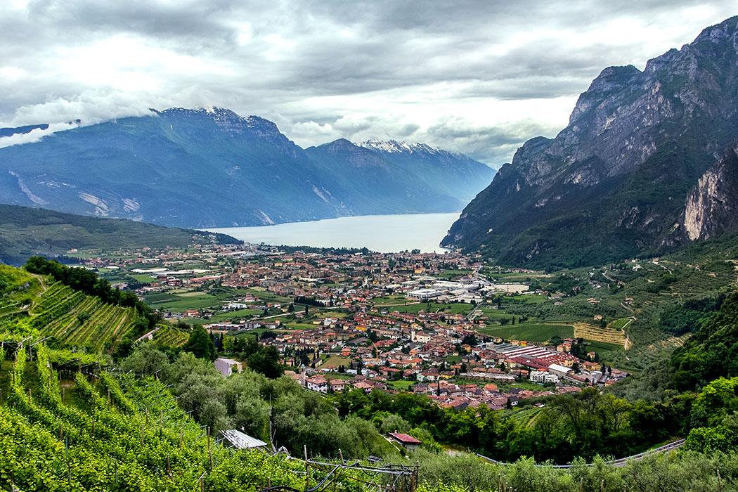 Garda Trentino: Tenno – Borgo mit Burgruine und Traumblick auf den Gardasee garda trentino tenno anfahrt riva del garda tenno weinberg gardasee italien Blick nach Riva del Garda vom wunderschönen Wanderweg durch die Weingärten hinauf nach Tenno. Etwas unterhalb verläuft die kurvenreiche Straße. Wir sind von Volta di No, kurz nach Cologna, gestartet.