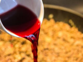 Eine Tasse trockenen Rotwein angießen.