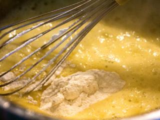 Langsam und unter ständigem Rühren mit dem Schneebesen, nach und nach die heiße Milch angießen.