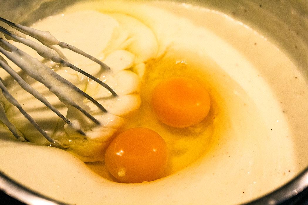 Wenn die Bechamel-Sauce abgekühlt ist, zwei Eier verquirlen und unter die Sauce rühren.
