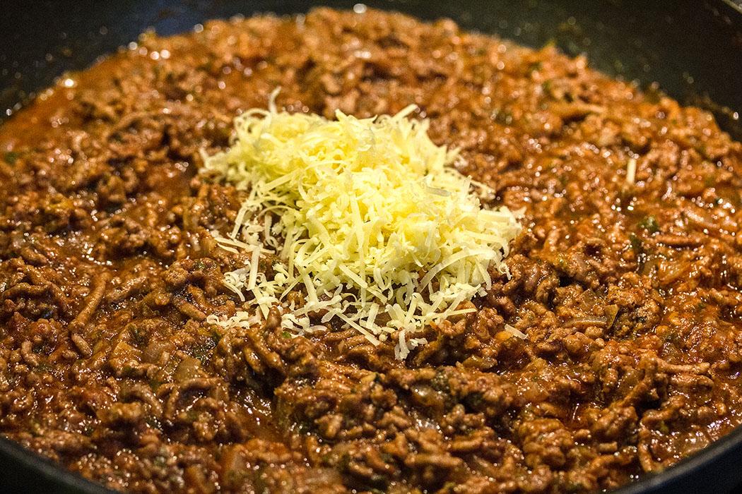 Nachdem die Hackfleisch-Sauce abgekühlt ist geriebenen Käse und ein Ei unterrühren.