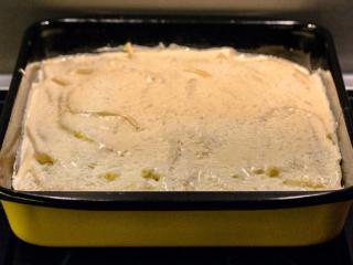 Zum Abschluß die Bechamel-Sauce über den Pastitsio gießen, gleichmässig verteilen und mit dem restlichen Käse bestreuen.