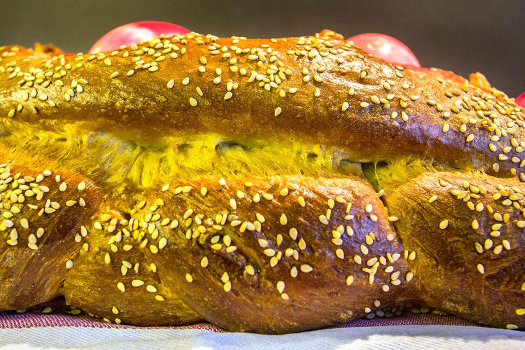 Griechisches Osterbrot: Tsoureki mit roten Ostereiern Griechisches Osterbrot, Tsoureki 01 Ist der Tsoureki fertig gebacken, ist er außen goldgelb und knusprig. Sein Inneres ist weich, fluffig und schmeckt aromatisch, durch die Zugabe von verschiedenen Gewürzen und Zitrusschalen-Abrieb.
