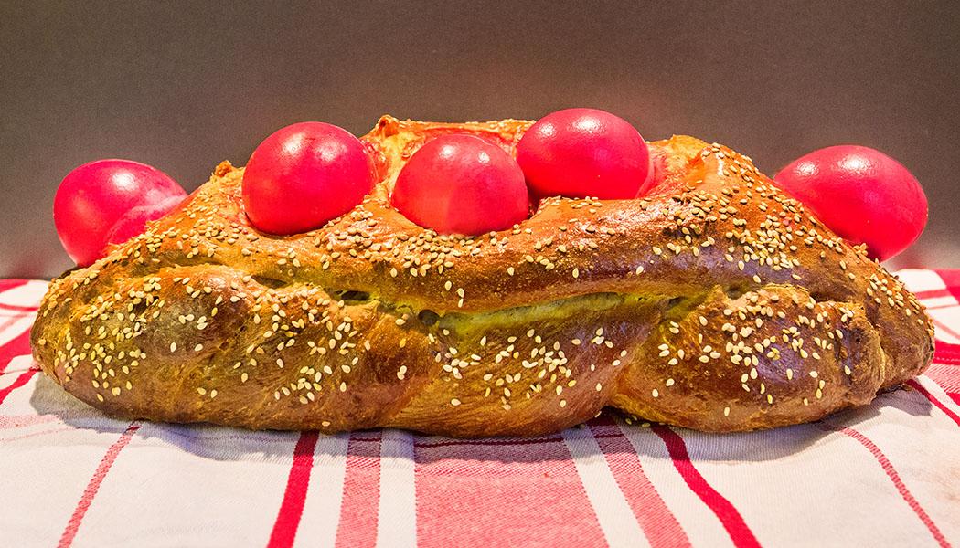 Griechisches Osterbrot, Tsoureki, Titel Griechisches Osterbrot: Tsoureki mit roten Ostereiern. Traditionell bekommt es seinen typischen Geschmack von den Gewürzen Machlepi und Mastix. Der Hefezopf gelingt leicht, braucht aber Zeit.