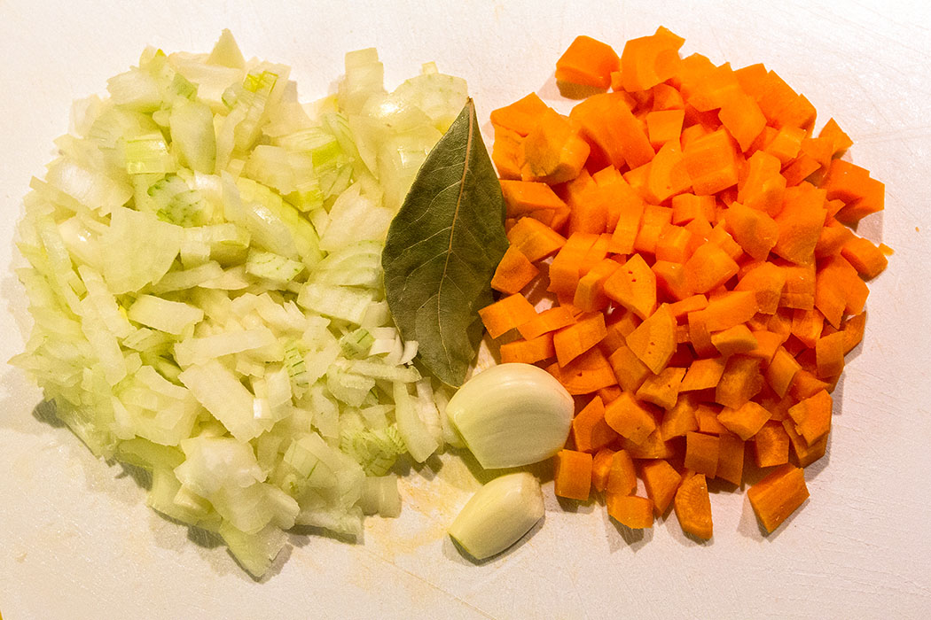 Zwiebeln und Karotten putzen, schälen und fein würfeln. Knoblauchzehen und Lorbeerblatt bereitlegen.