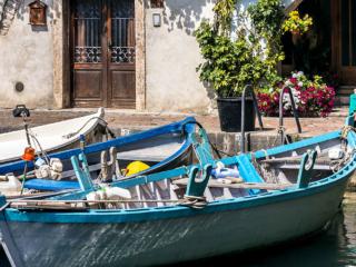 Traditionelle Holzboote im Hafenbecken von Cassone.