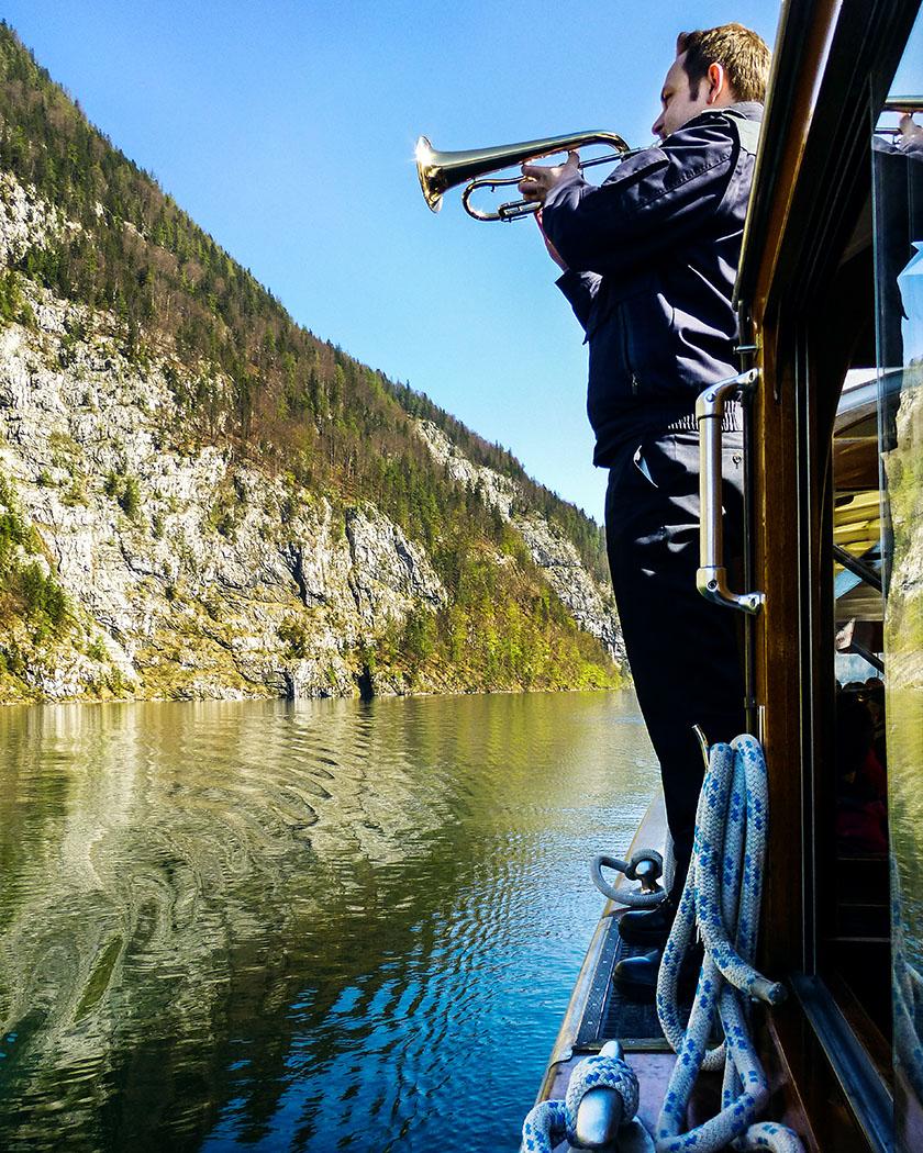 """Deutschland, Oberbayern, Nationalpark Berchtesgaden, Koenigssee, Echowand, Schoenau, Bootsfahrt, April 2017 - Atemlose Stille im Boot: Unser Bootsbegleiter führt uns mit wunderbarem Trompetenspiel das Echo an der """"Echowand"""" vor."""