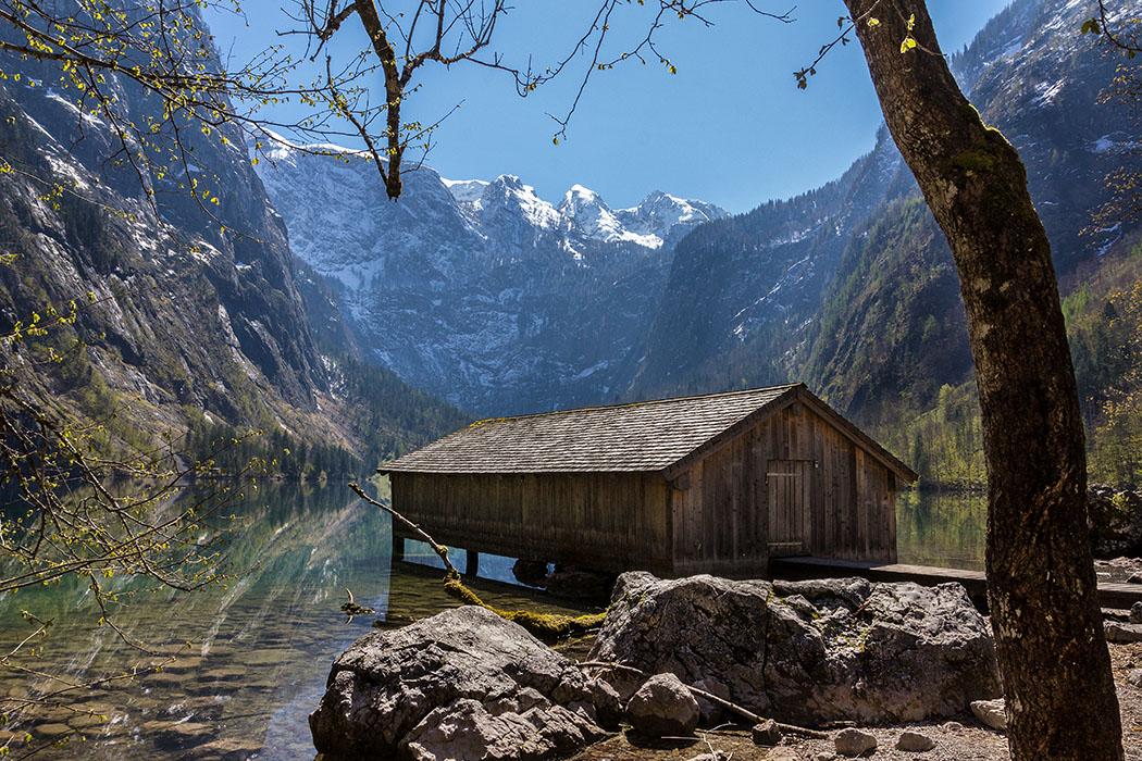 Oberbayern: Königssee - Von Salet zur Fischunkelalm am Obersee - Deutschland, Oberbayern, Nationalpark Berchtesgaden, Obersee, Bootshaus, April 2017 - Zur Fischunkelalm am Obersee pendeln die Almbauern mit Schiffen über die beiden Bootshäuser hinüber. Die beiden Bootshäuser gehören der Nationalparkverwaltung Berchtesgaden.