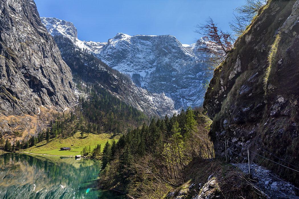 Oberbayern: Königssee - Von Salet zur Fischunkelalm am Obersee - Deutschland, Oberbayern, Nationalpark Berchtesgaden, Obersee, Fischunkelalm, Felsensteig Walchhüttenwand, April 2017 - Auf dem Weg entlang des Obersees zur Fischunkelalm muss eine Felsenstufe mit Auf- und Abstieg überwunden werden. Ist dem höchsten Punkt bietet sich eine gewaltige Bergkulisse mit Sicht auf die Alm und das Bootshaus.