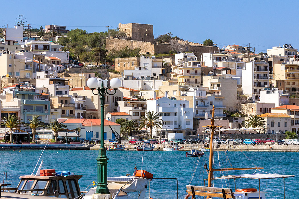 """Ostkreta: Sitia - Entspannter Flair in Kretas östlichster Hafenstadt - Griechenland, Kreta, Osten, Sitia, Stadt, Lasithi, Hafen, Burg, Fischerboote - Sitia ist ein attraktives Hafenstädtchen im Osten der Insel Kreta. Mit etwa 300 Sonnenstunden im Jahr ist der Ort besonders für Nordeuropäer ein Traumziel. Die Häuser sind terrassenförmig an den Hang gebaut und werden von der venezianischen Festung """"Kazarma"""" überragt."""