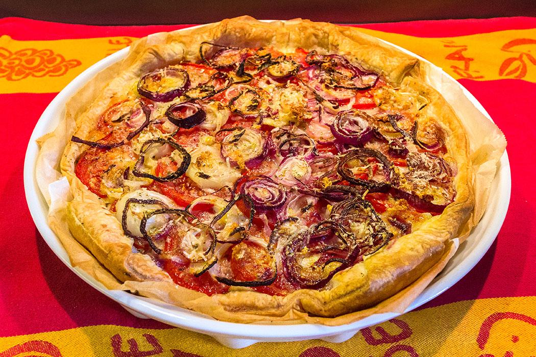 Die Blätterteig-Quiche mit Tomaten, Zwiebeln und Knoblauch in der Backform noch etwa 10 Minuten abkühlen lassen.