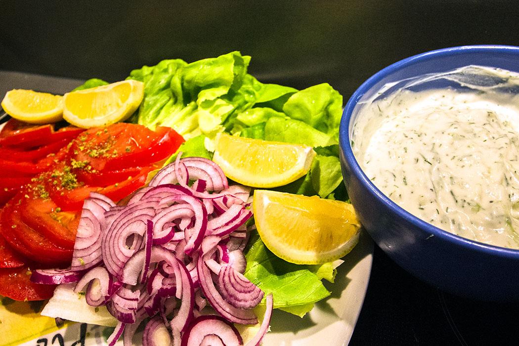 Auf einer Servierplatte Tomaten in Scheiben, rote Zwiebel in Streifen, etwas Blattsalat und Zitronenschnitze anrichten.