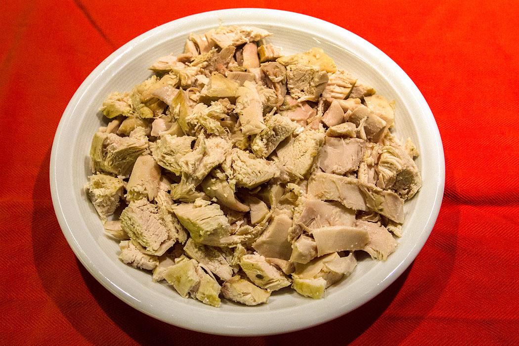 Hühnchenfleisch auskühlen lassen. Die Haut entfernen, das Fleisch in kleine Stücke würfeln.