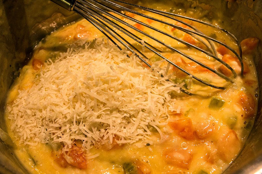 In einer Schüssel in die Bechamelsauce Eier einrühren. Dann geriebenen Käse, Gemüse, Kräuter und Hühnerfleisch dazugeben und verrühren.