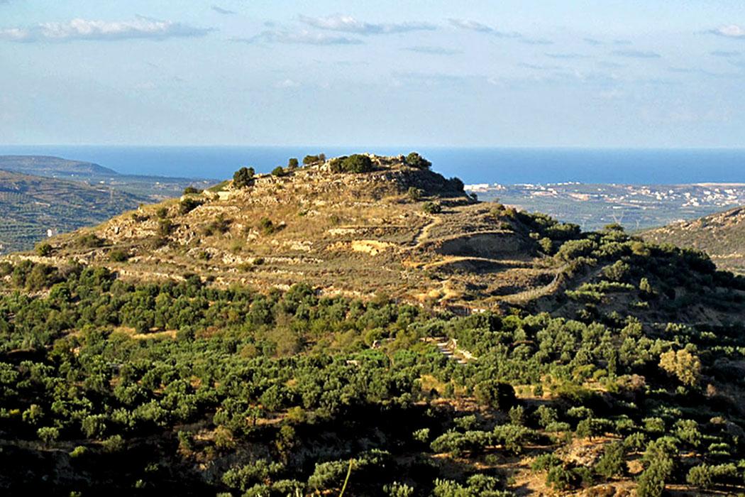 """crete_praisos_first_acropolis_sitia-01_ol - Blick von Nea Praisos auf den Hügel mit der """"Ersten Akropolis"""" der antiken Stadt Praisos, im Hintergrund ist Sitia sichtbar."""