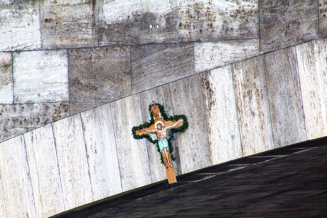 An einem schmalen Seil wird das Kreuz aus der Isar gezogen.