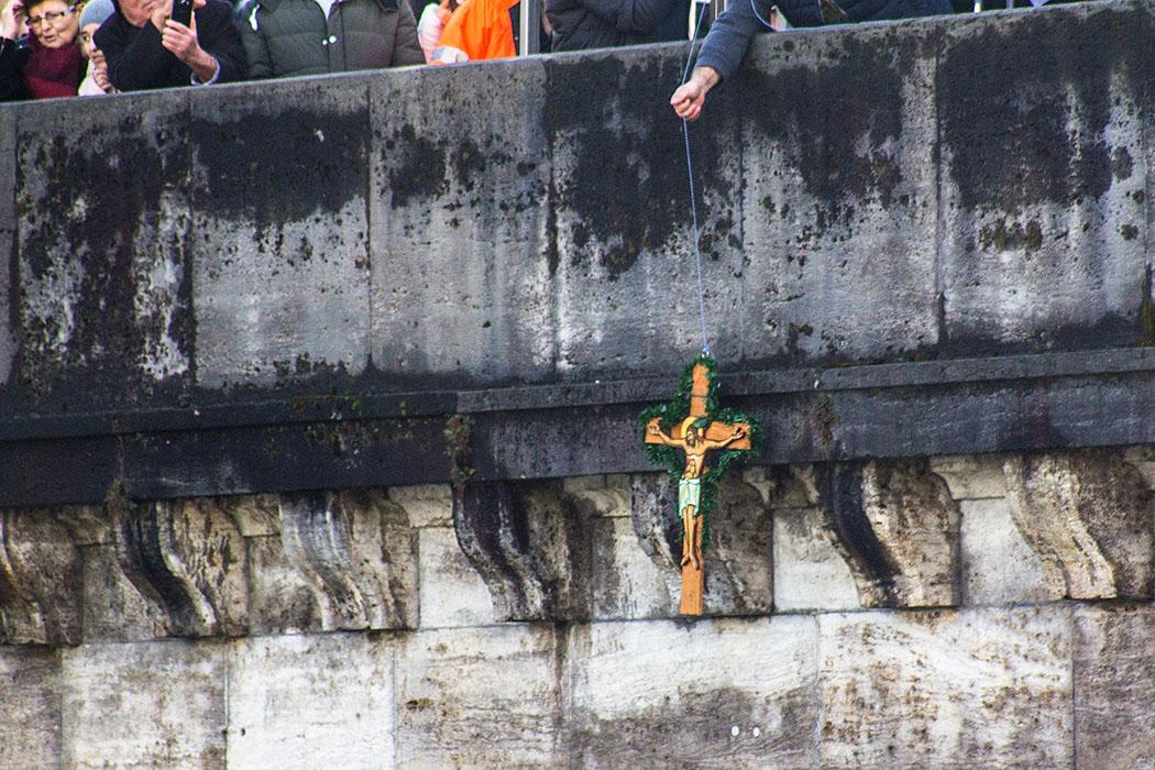 Das Kreuz ist fast geborgen, die Hand eines freiwilligen Helfers greift von oben danach.