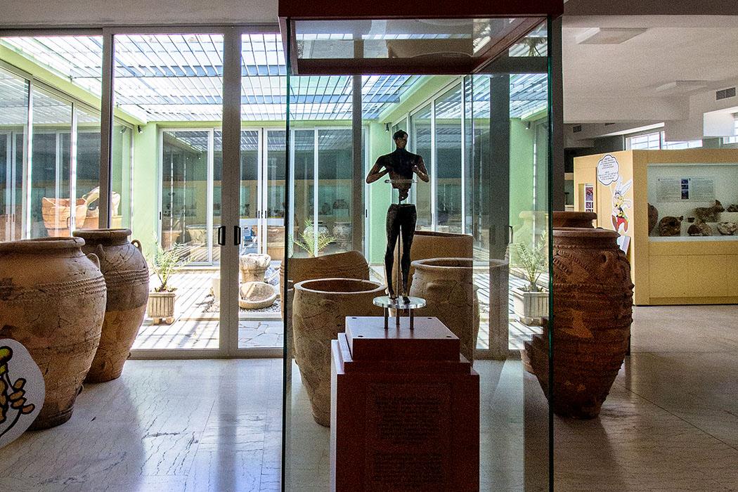 """reise-zikaden.de, Monika Hoffmann, greece, griechenland, crete, kreta, sitia, siteia, archaeological museum, kouros of palekastro - Der """"Kouros von Palekastro"""" ist das wertvollste Fundstück im Archäologischen Museum von Sitia. Die minoische Statuette stammt aus spätminoischer Zeit und datiert auf das 15. Jhd. v. Chr. Sie wurde in 1990er-Jahren bei Ausgrabungen in Roussolakkos bei Palekastro gefunden."""