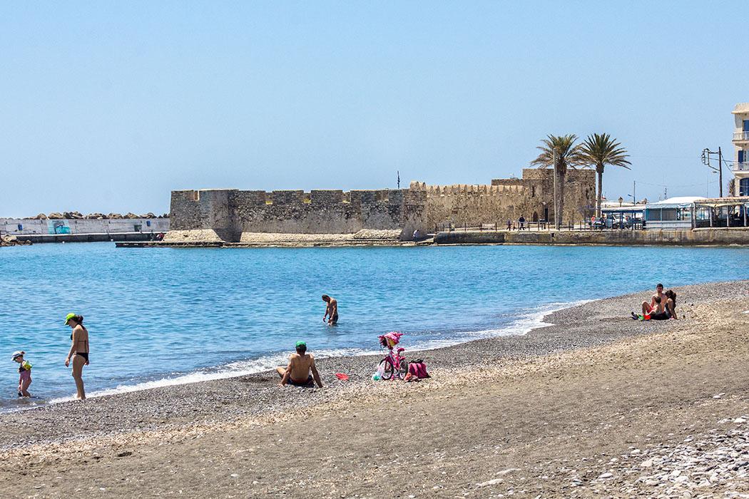 Der gepflegte Sand-Kieselstrand beginnt im Zentrum von Ierapetra. Der flachabfallende Strand ist auch für Kinder ideal. Im Hintergrund das Hafenkastell Fort Kalés aus dem 13. Jhd.