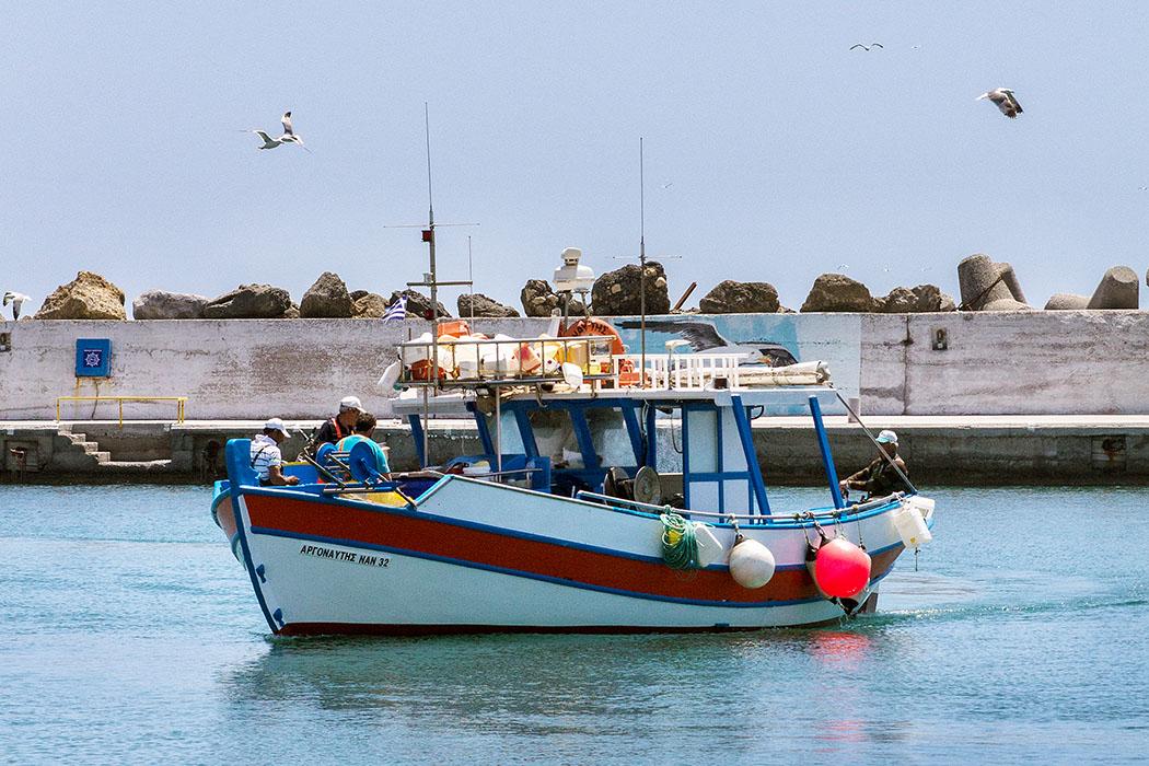 Ein Fischerboot mit fünf Männern Besatzung kommt um die Mittagszeit von seiner Ausfahrt in den Hafen von Ierapetra zurück.