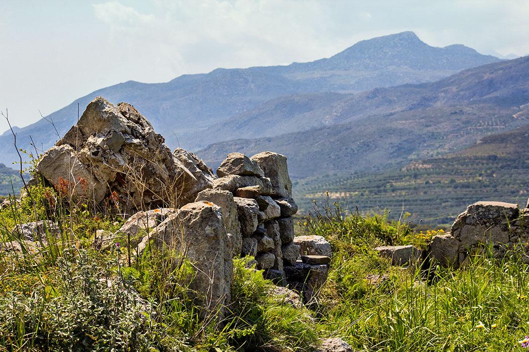 """reise-zikaden.de, greece, griechenland, crete, kreta, lasithi, sitia, praisos, first akropolis, zeus temple - Die Fundamente des Zeus-Tempels auf der """"Ersten Akropolis"""" sind weitgehend überwachsen. Die fantastischen Aussichten auf die Berge des Thripti-Gebirges sind eine perfekte Entschädigung."""