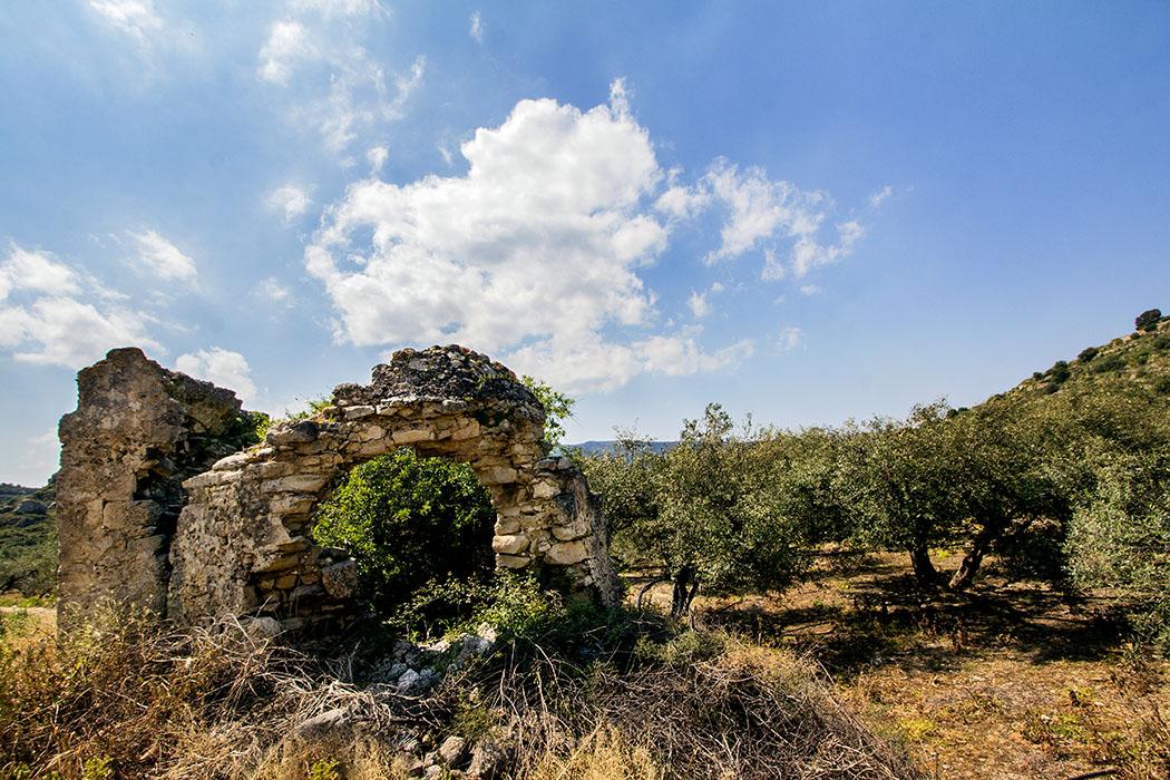 """reise-zikaden.de, greece, griechenland, crete, kreta, lasithi, sitia, praisos, ruins, house - Ruinen von Wohngebäuden sind überall in der Ebene zu finden. Neben dem Fahrweg befinden sich die Mauern eine Kirchenruine. Rechts im Bild ist die """"Erste Akropolis"""" sichtbar."""