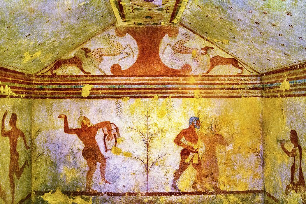 reise-zikaden.de, Italien, Tarquinia, Monterozzi Nekorpole, Tomba dei Baccanti - Die Tomba dei Baccanti zeigt im Giebelfeld Löwen die Gazellen angreifen und datiert auf den Zeitraum 520 bis 500 v. Chr. Im linken Bereich ist ein Lyraspieler zu sehen, rechts ein tanzendes Paar.