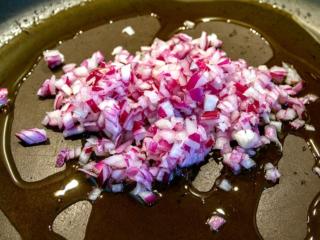 Rote Zwiebel fein hacken und in Olivenöl anbraten.