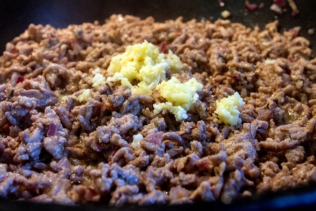 Hackfleisch mit Kräutern und Peperoncino anbraten. Knoblauch kurz mit braten.