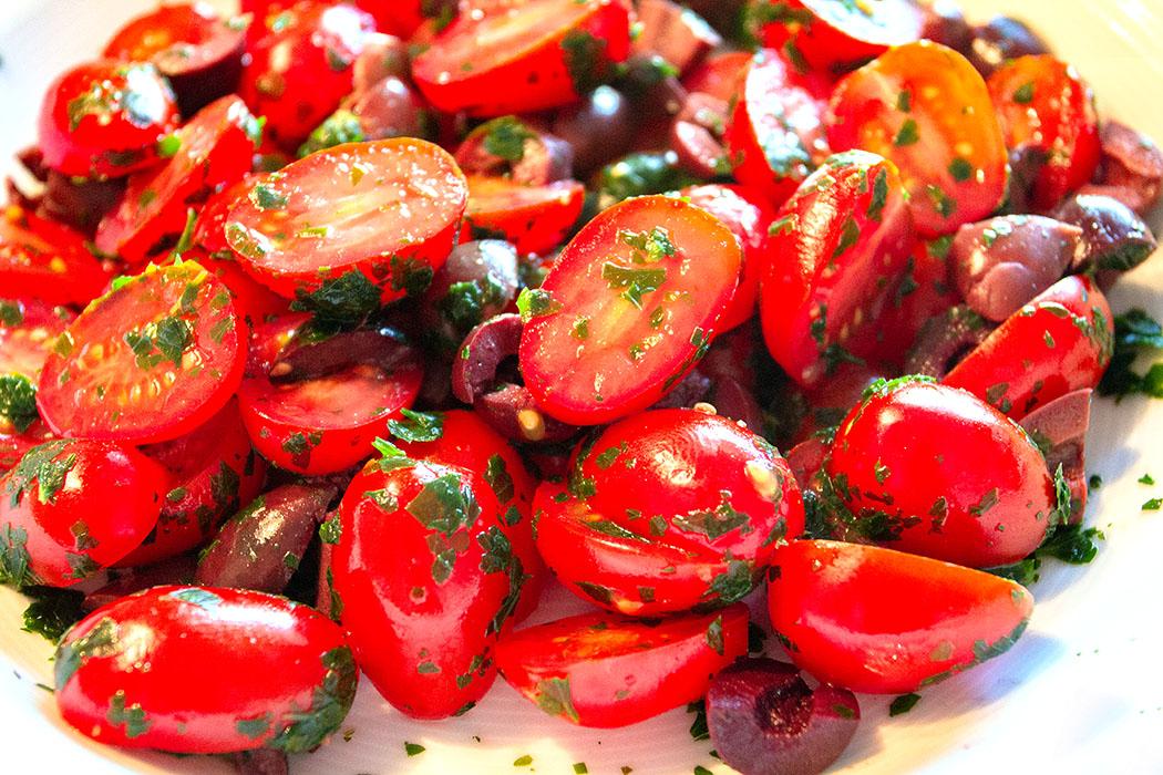 Kirschtomaten halbieren, mit gehackter Petersilie, Olivenwürfel, Salz und Pfeffer mischen.
