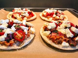 Pizzen mit Hackfleisch und Mozzarella belegen. Darüber die Kirsch-Tomaten-Oliven-Mischung geben.