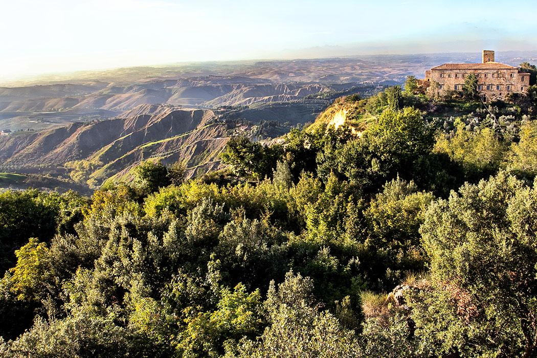 """Toskana: Cicero und die etruskische Familie Caecina aus Volterra - reise-zikaden.de, italy, italien, tuscany, toskana, volterra, Balze, Badia Camaldolese - Inmitten eines zerfurchten, kargen Hügelgebiets liegt Volterra auf einem Bergrücken. Das Gebiet im Westen wird """"Le Balze"""" genannt, dort haben Erdschübe Teile der etruskischen Stadtmauern und Nekropolen in die Tiefe gerissen. Nahe des Abgrunds steht die Ruine der Badia, eine Camaldulenser-Abtei von 1030."""